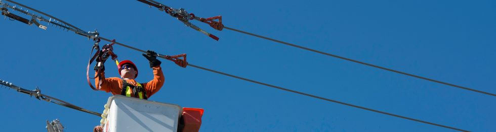 Banner image of powerline technician working on a powerline